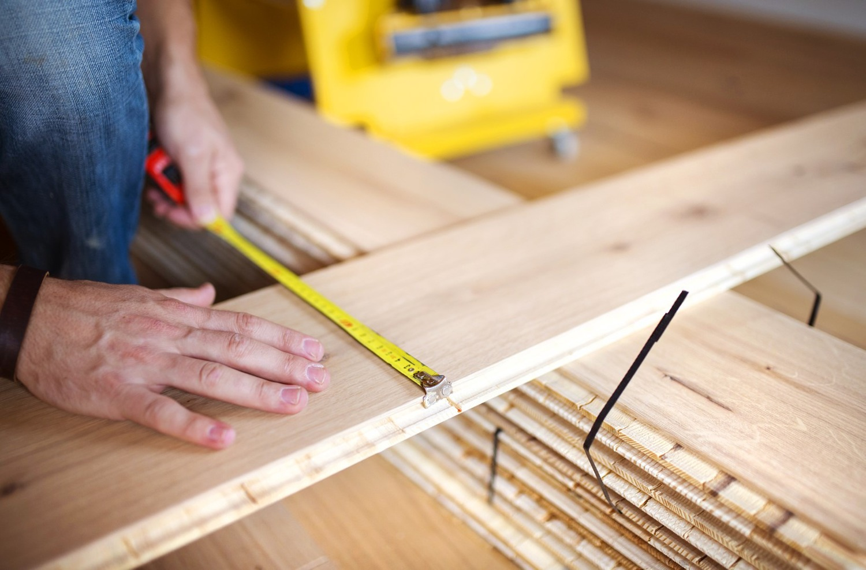 Close up of handymans hands measuring wood flooring