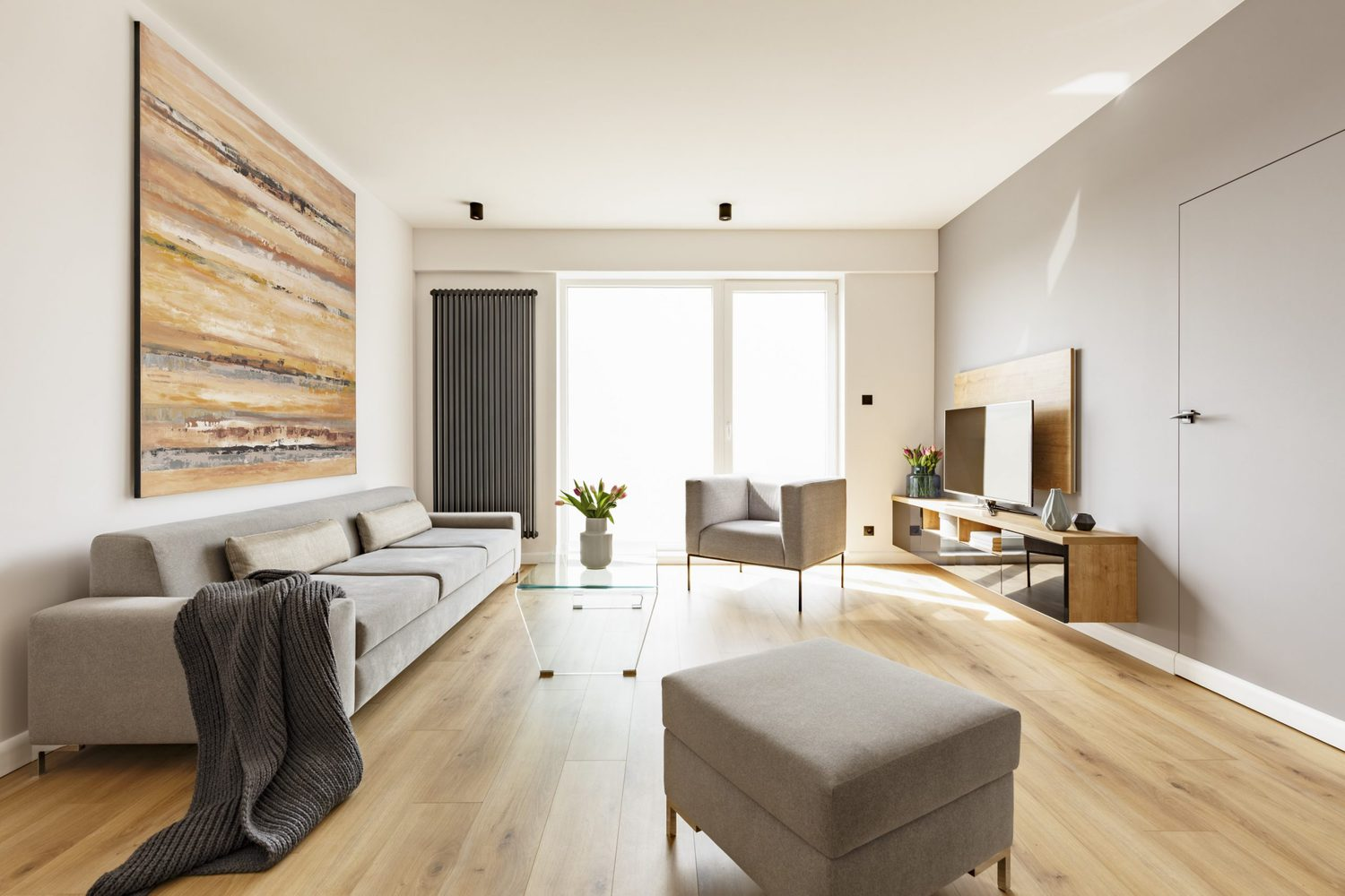 Modern apartment interior with a grey sofa, footstool and armcha